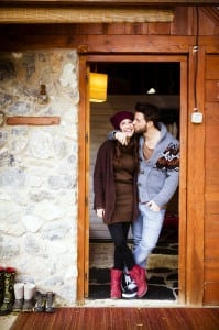 Couple standing by the cabin door with guy kissing girl on the cheek