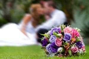 pink and purple bouquet with newlyweds in background