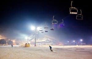 Ski resort at night with man snowboarding