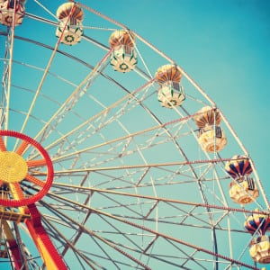 Vintage style photo of ferris wheel in blue sky