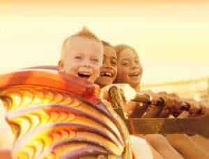 Kids riding roller coaster in the sunset