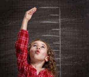 Girl measuring how tall she is against a black board