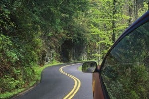 Car driving on a scenic road to a Great Smoky Mountains National Park visitor center.