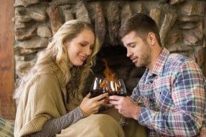 A romantic couple enjoying wine in front of a cabin fireplace.