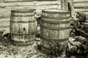 Old water barrels outside of a log cabin.