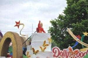 Dolly Parton waving to her fans from the Dollywood float in her annual parade.