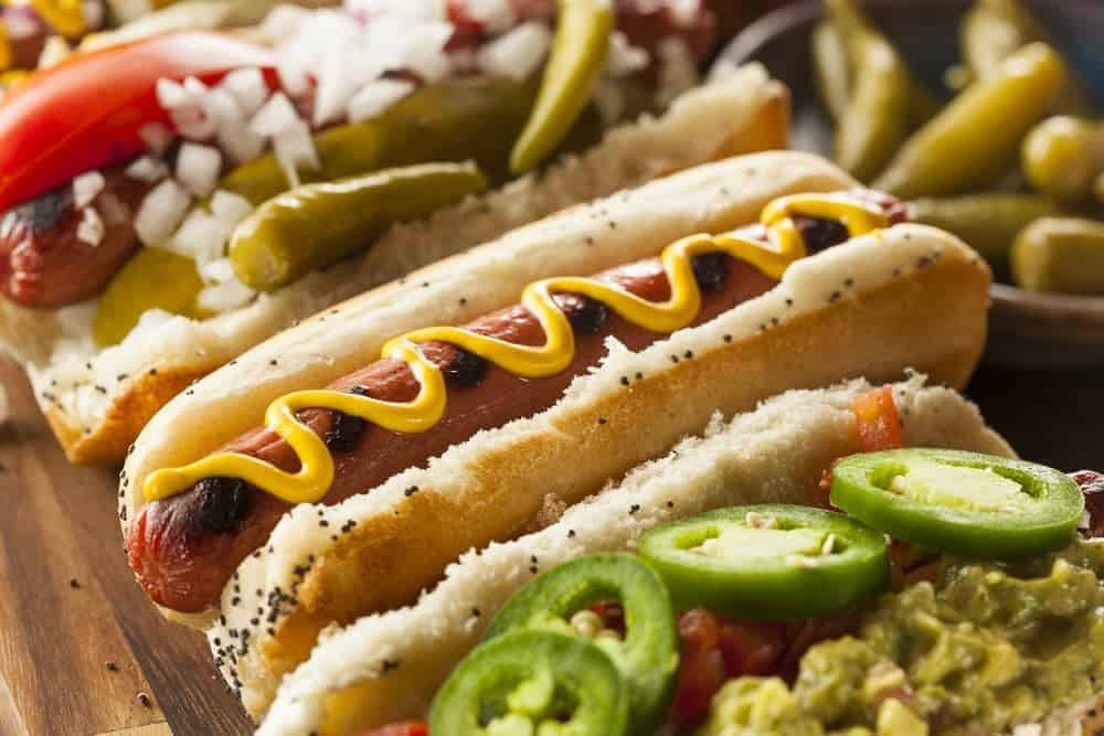 A row of gourmet hot dogs with lots of toppings.