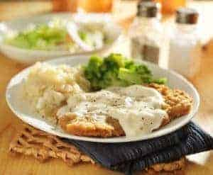 Country fried steak with gravy and sides.